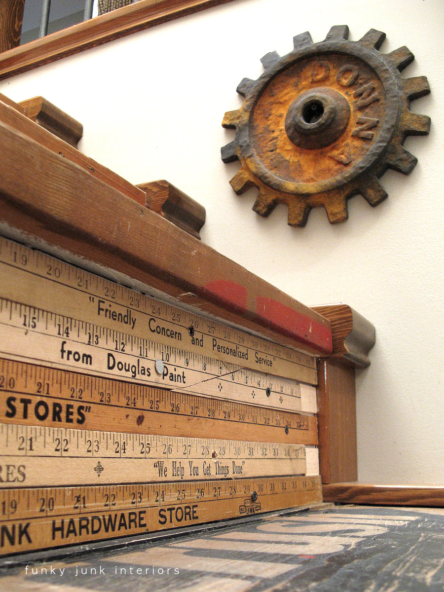Yardstick stairway risers, gear wall art, along stairway, part of a whole home JUNK tour via Funky Junk Interiors