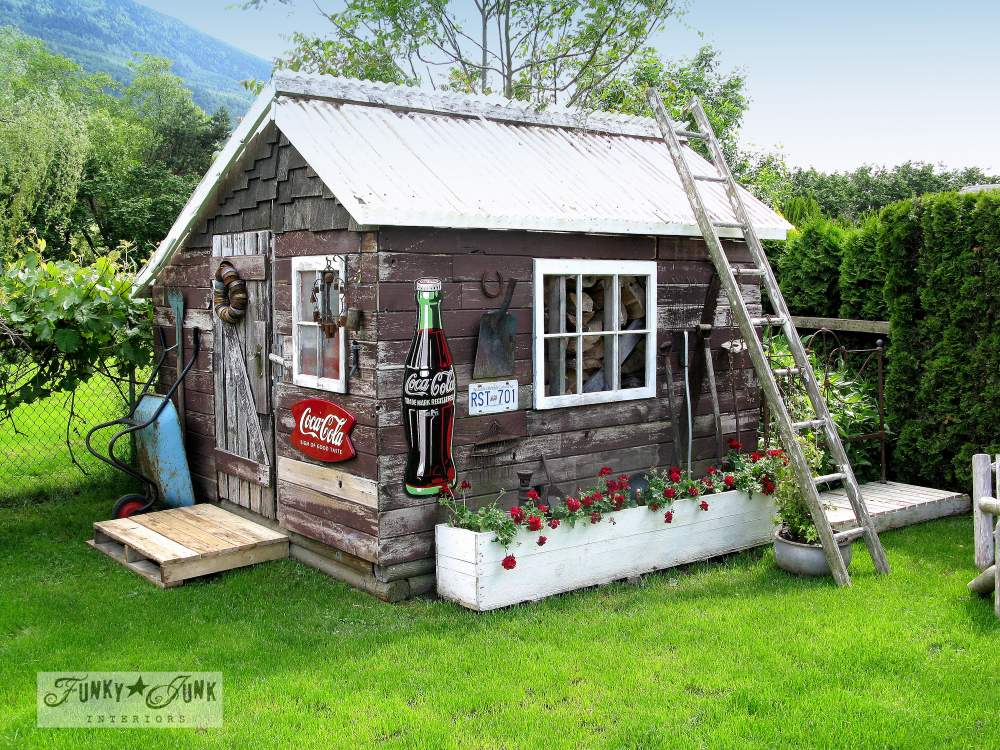 Rustic garden shed decorated with old reclaimed wood fence boards and junk, with pallet walkway, via Funky Junk Interiors
