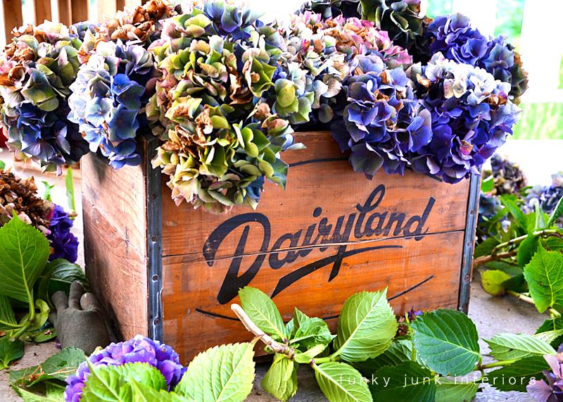 Arrange abundant hydrangea blooms inside antique crates with jars of water for amazing summer impact! Part of - Try these up-cycled finds as vases for unique flower arrangements!