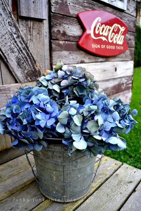 Layering galvanized pots doubles the rustic fun for this hydrangea flower vignette! Part of - Try these up-cycled finds as vases for unique flower arrangements!