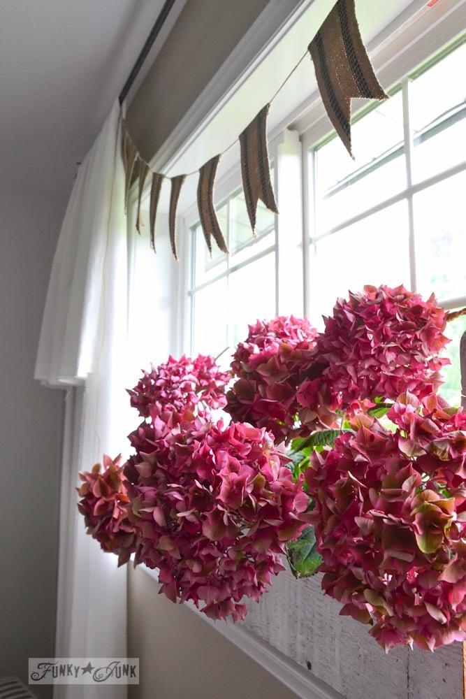 Pink hydrangeas on window sill in toolbox, webbing garland via Funky Junk Interiors