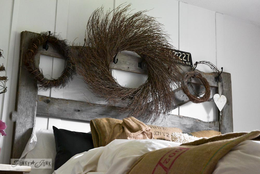 Rustic wreaths on a horse gate headboard in master bedroom via Funky Junk Interiors