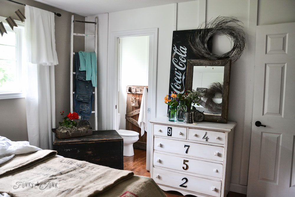 Ladder jeans hanger and white numbered dresser with coke sign in master bedroom, via Funky Junk Interiors