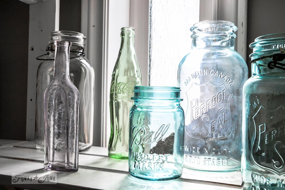 Vintage bottles and mason jars in the sunlight, part of a junky decorating office redo via Funky Junk Interiors