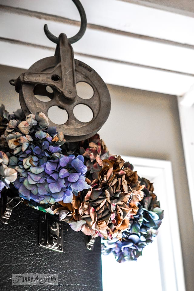 Dried hydrangeas in a vintage suitcase and clothes line wheel, part of a junky decorating office redo via Funky Junk Interiors