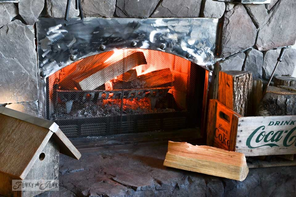 Real wood burning fireplace with a curved industrial metal plate / part of The first cozy fireplace fire of the season via https://www.funkyjunkinteriors.net/