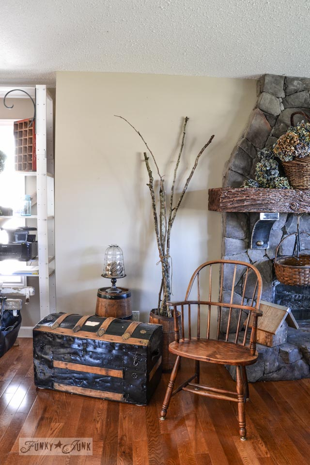 Old trunk for firewood, two old barrels, cloche, sticks and bentwood chair - part of a funky wall cabinet gallery reveal via : https://www.funkyjunkinteriors.net/