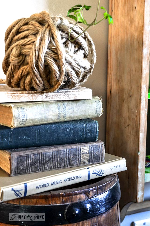Stacked old books and twine wrapped orb - part of a funky wall cabinet gallery reveal via : http://www.funkyjunkinteriors.net/
