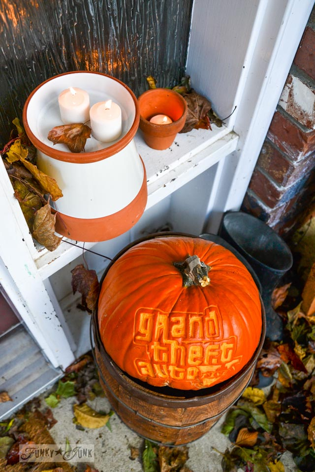 clay pots with candles and Grand Theft Auto logo carved in pumpkin  / Happy cheater Halloween decorating! No carving required. via https://www.funkyjunkinteriors.net/