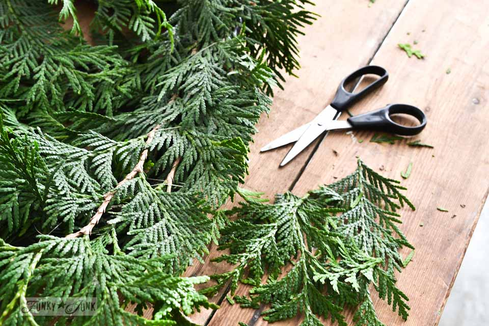 Trimming evergreen branches / How to make a square evergreen wreath on a picture frame. So easy! via https://www.funkyjunkinteriors.net/