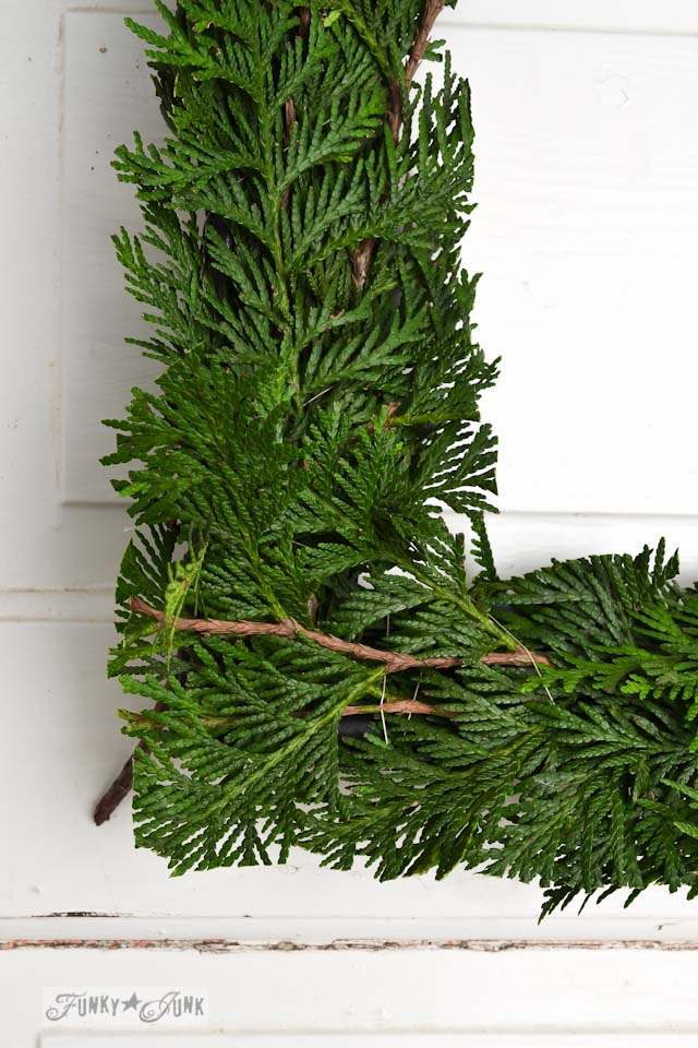 Trimming evergreen branches square / How to make a square evergreen wreath on a picture frame. So easy!  via https://www.funkyjunkinteriors.net/