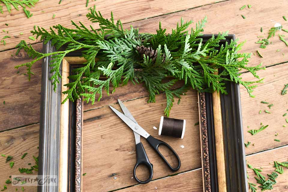 Evergreen spray with floral wire / How to make a square evergreen wreath on a picture frame. So easy!  via https://www.funkyjunkinteriors.net/