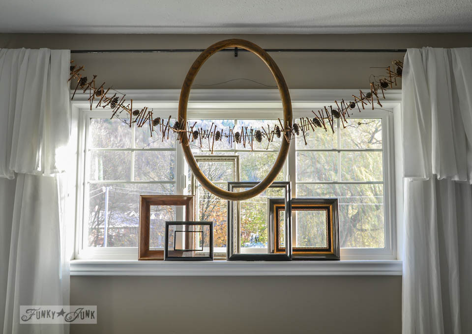 Windowsill decor with empty frames and garland / How to make a square evergreen wreath on a picture frame. So easy!  via https://www.funkyjunkinteriors.net/