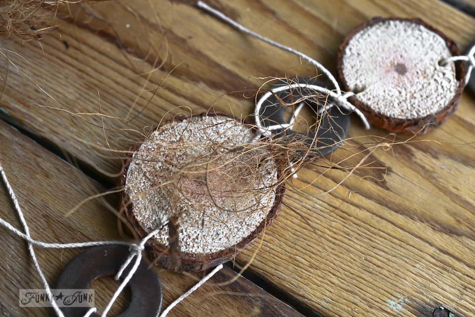 Attaching coco fiber onto garland / Cool and quirky fuzzy wood round and metal washer Christmas garland via https://www.funkyjunkinteriors.net/