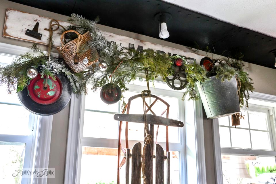 Wheel wreath valance / A well lit junky Christmas kitchen / salvaged finds used to deck out this kitchen for Christmas via http://www.funkyjunkinteriors.net/