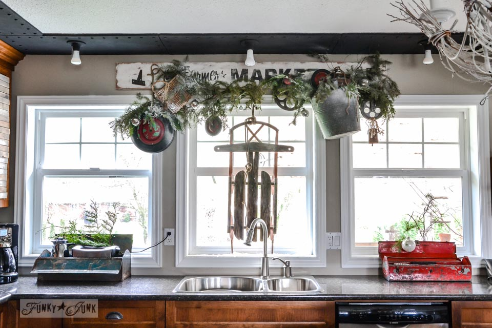 Christmas junk wheel wreath valance and sleigh in window / A junky Christmas kitchen / salvaged finds used to deck out this kitchen for Christmas via http://www.funkyjunkinteriors.net/