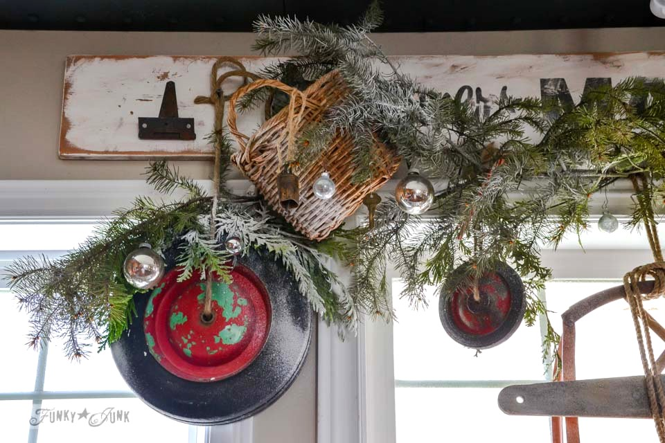 Christmas junk wheel wreath valance / A well lit junky Christmas kitchen / salvaged finds used to deck out this kitchen for Christmas via https://www.funkyjunkinteriors.net/