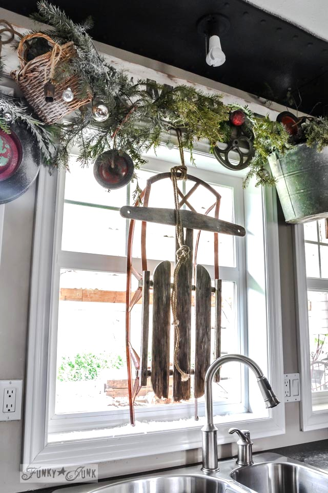 Christmas junk wheel wreath valance and sleigh in window / A junky Christmas kitchen / salvaged finds used to deck out this kitchen for Christmas via https://www.funkyjunkinteriors.net/
