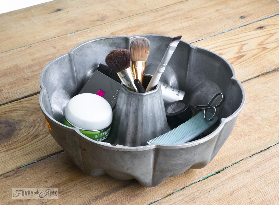 Antique cake pan for makeup storage / A little new old upcycled bathroom organizing via https://www.funkyjunkinteriors.net/