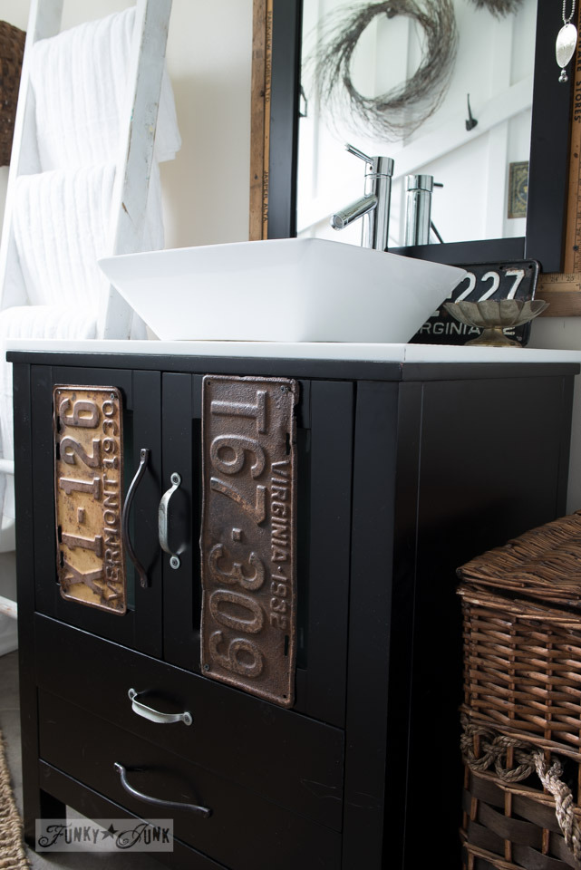 Vintage license plates on black vanity with vessel sink / Salvaged farmhouse bathroom makeover via https://www.funkyjunkinteriors.net/