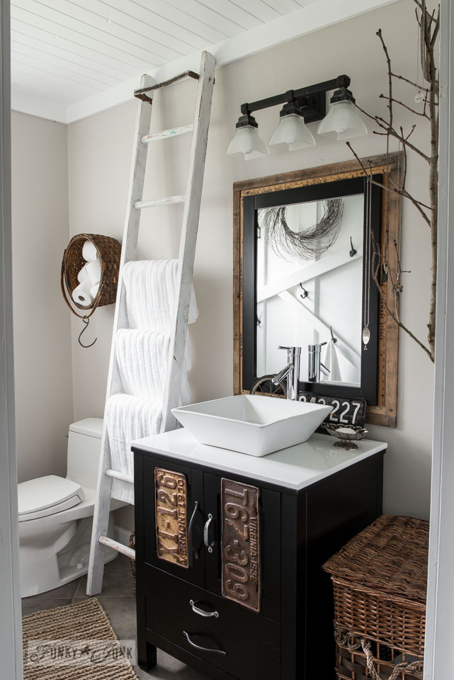 Salvaged Farmhouse bathroom makeover with yardstick mirror, ladder towel storage and planked over popcorn ceiling