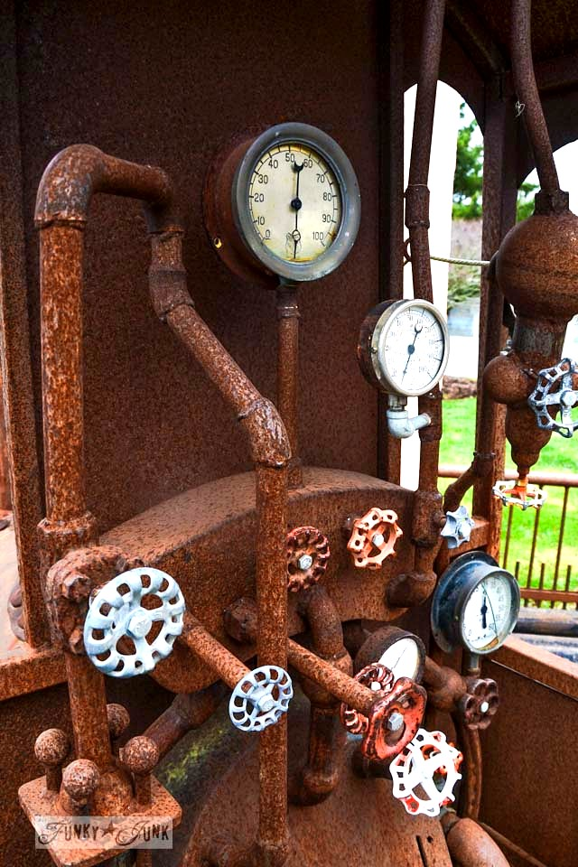 Rusted mini train with taps and dials / A rusty train with vintage tap handle gears / Someone's got a serious Imagination Corporation! via https://www.funkyjunkinteriors.net/