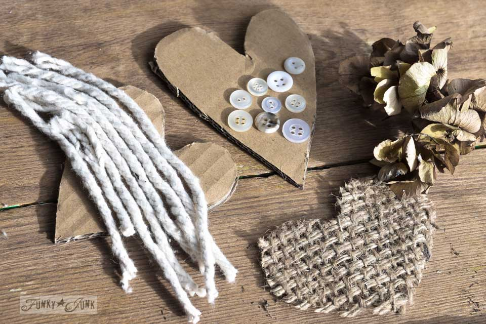 Gluing embellishments onto cardboard / Learn how to make these charming rustic hearts for Valentine's Day with bark, twine, burlap, buttons, plus! Click for full tutorial with many ideas! #valentinesday #hearts #valentines #funkyjunkinteriors #repurpose