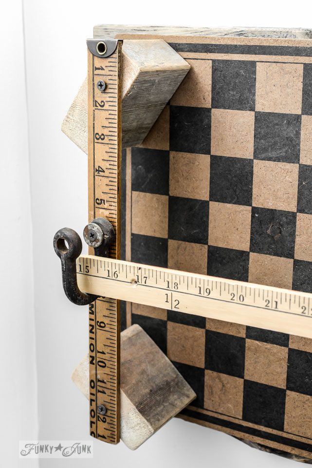 Make a checkerboard yardstick toilet paper holder for a rustic bathroom via FunkyJunkInteriors