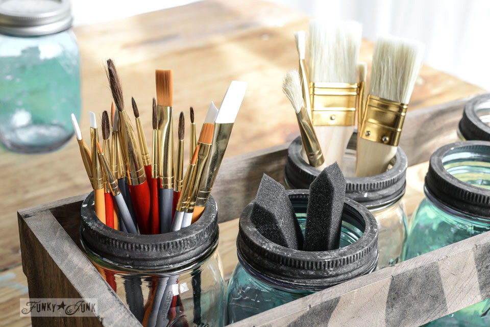 Crate of mason jars holding artist paint brushes from Michaels via FunkyJunkInteriors.net