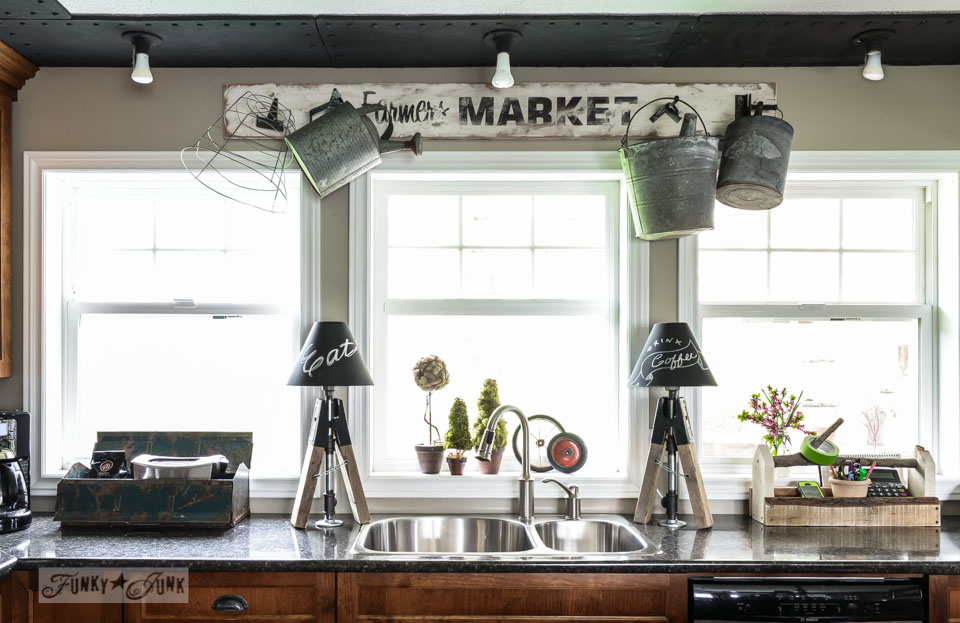 Rustic kitchen with sign and sawhorse pipe lamps via FunkyJunkInteriors.net