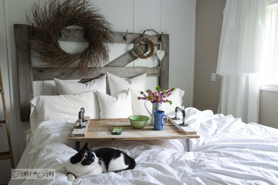 Pipe handled bedtray in a white rustic bedroom with horse gate headboard | funkyunkinteriors.net