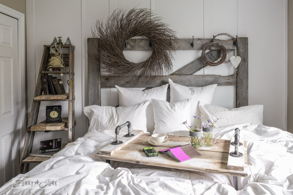 Industrial wood and pipe bed tray and horse gate headboard with wreaths / Make a stepladder side table via FunkyJunkInteriors.net