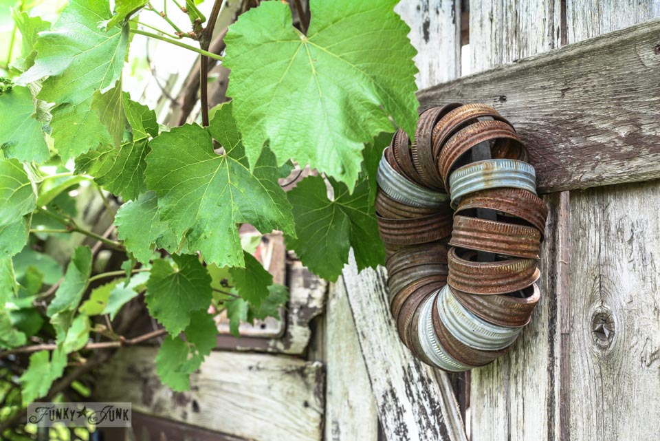 Rusty canning jar wreath on a shed / Rustic garden shed with old signs, tools and a grapevine, on FunkyJunkInteriors.net