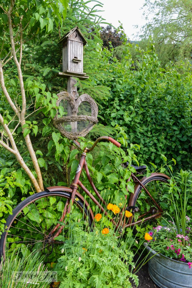 Old vintage bike in a garden via FunkyJunkInteriors.net