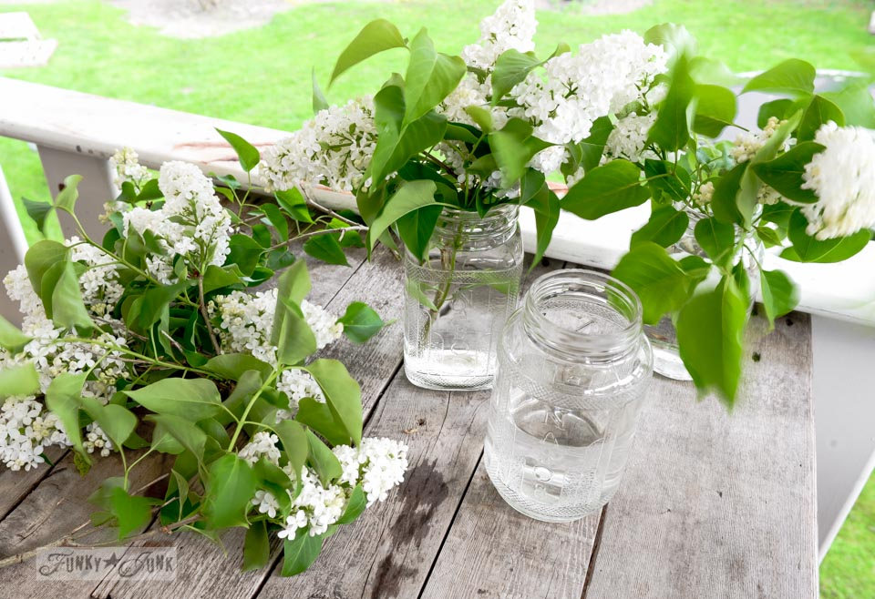 White lilacs in mason jars / Mantel decorating with a lilac filled junky toolbox planter, with wheels and vintage tap handles via FunkyJunkInteriors.net