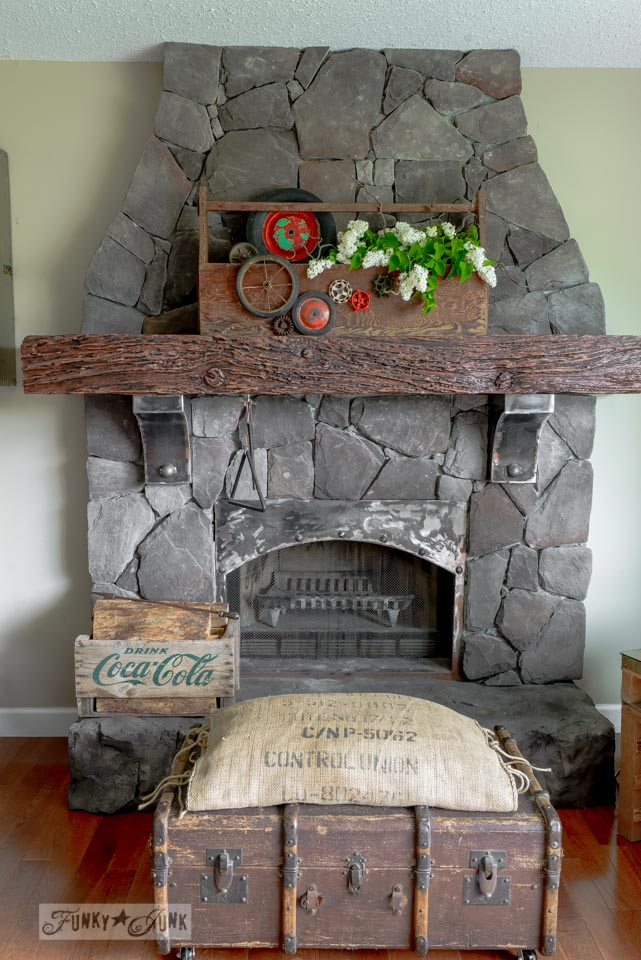 Rock fireplace with trunk ottoman and toolbox planter via FunkyJunkInteriors.net
