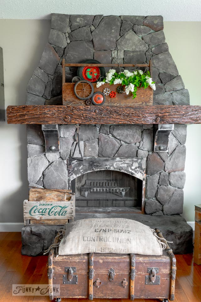 Mantel decorating with a lilac filled junky toolbox planter, with wheels and vintage tap handles via FunkyJunkInteriors.net