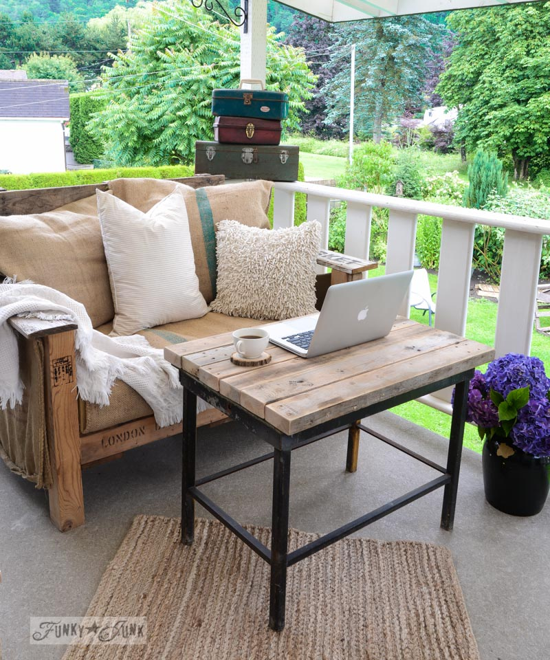 Pallet wood sofa on patio with laptop / FunkyJunkInteriors.net