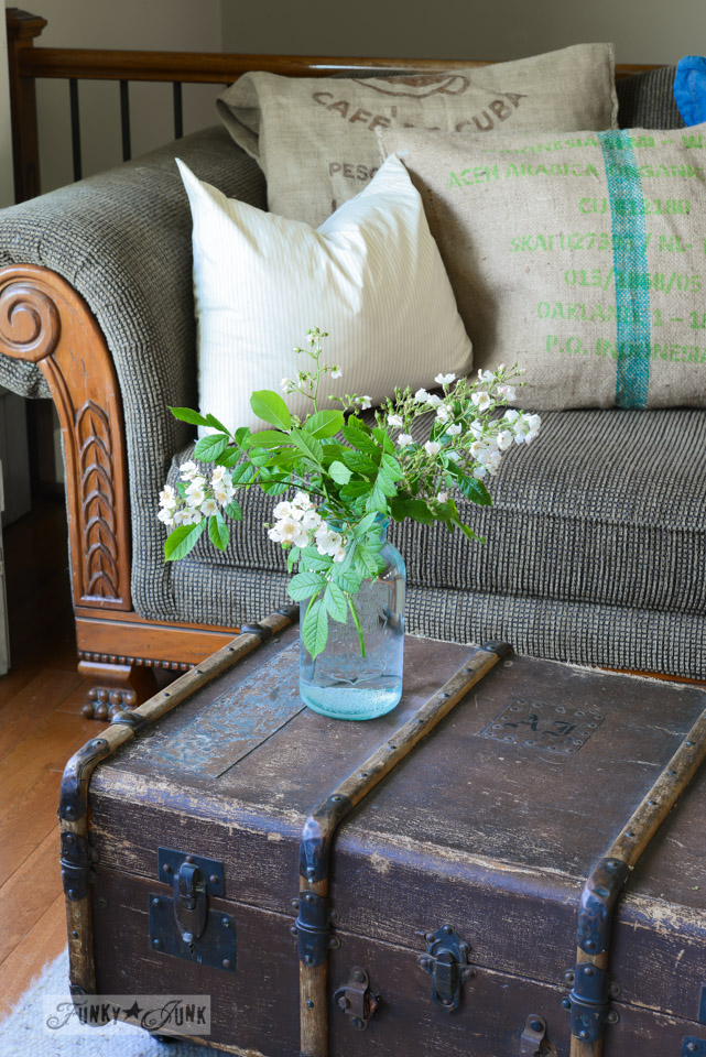 Aqua mason jar holding flowers on old trunk ottoman via FunkyJunkInteriors.net