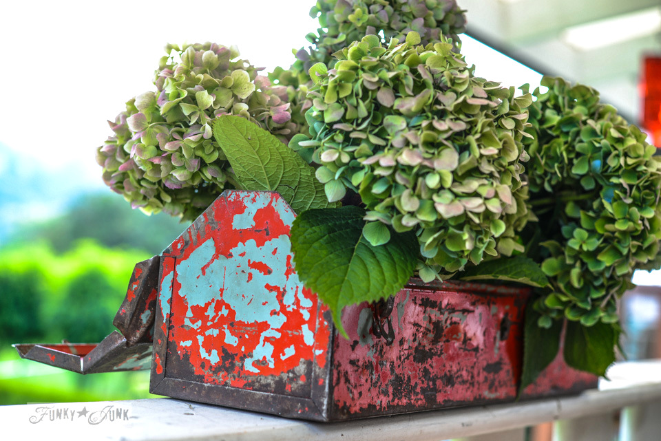 Green hydrangeas in a red toolbox / A milk painted pallet wood tray in tricycle / via FunkyJunkInteriors.net