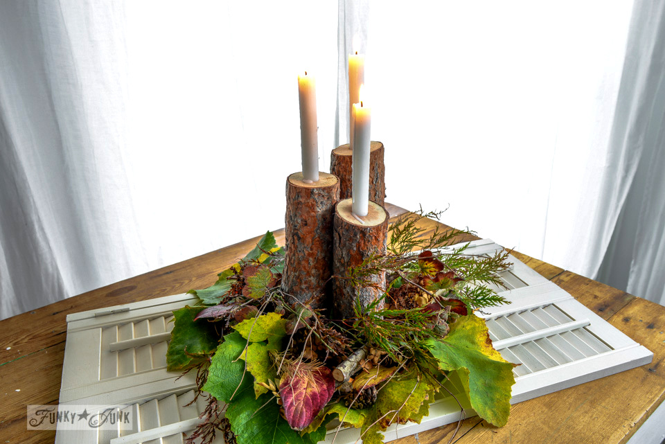A nature inspired, rustic log candle fall centrepiece on a shutter / FunkyJunkInteriors.net