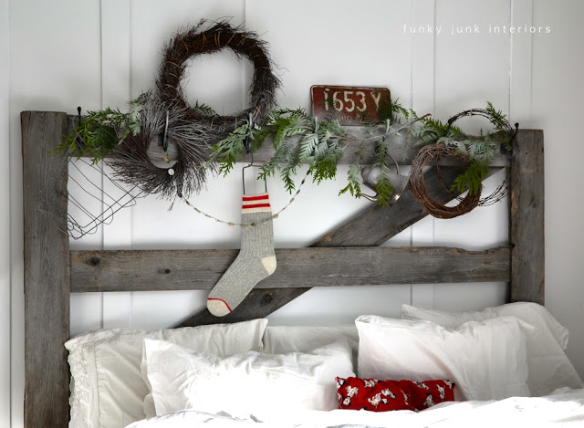 Christmas headboard with evergreen and button garland on FunkyJunkInteriors.net