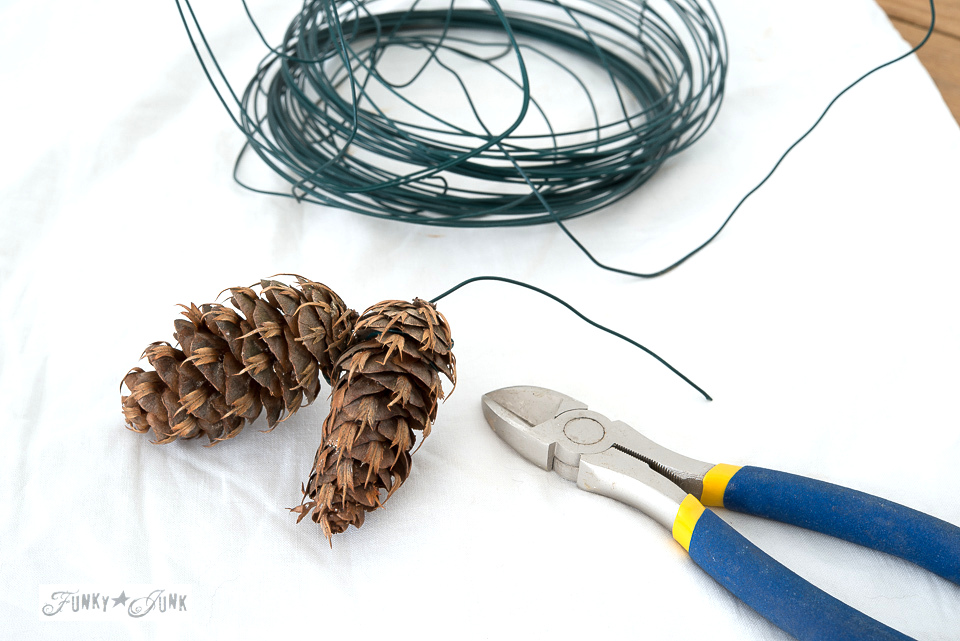 How to make an evergreen and pinecone swag using florist wire to add to an industrial mason rim Christmas tree ornament wreath! Click to read full tutorial.