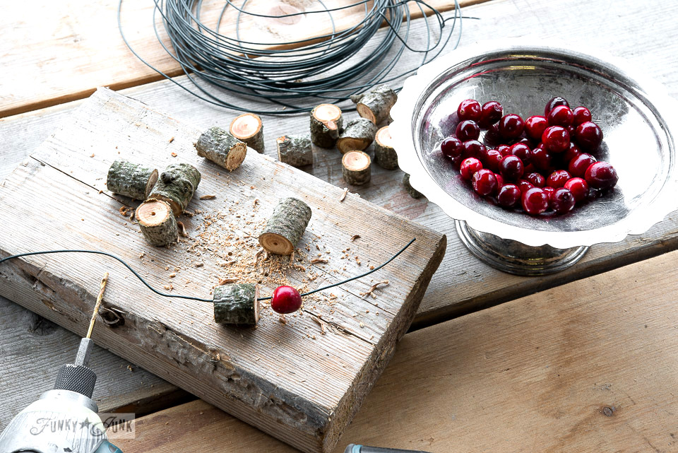 Cutting a branch / Wooden bead and cranberry Christmas wreath / FunkyJunkInteriors.net