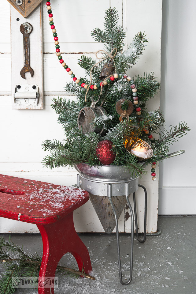With spray snow / Faux to real mini Christmas tree in a strainer with wooden presents, on FunkyJunkInteriors.net