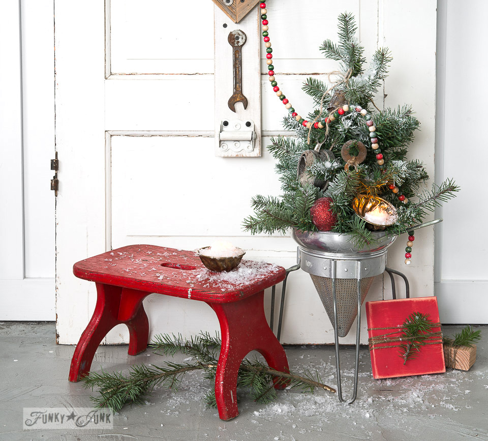 Faux to real mini Christmas tree in a strainer with wooden presents, on FunkyJunkInteriors.net
