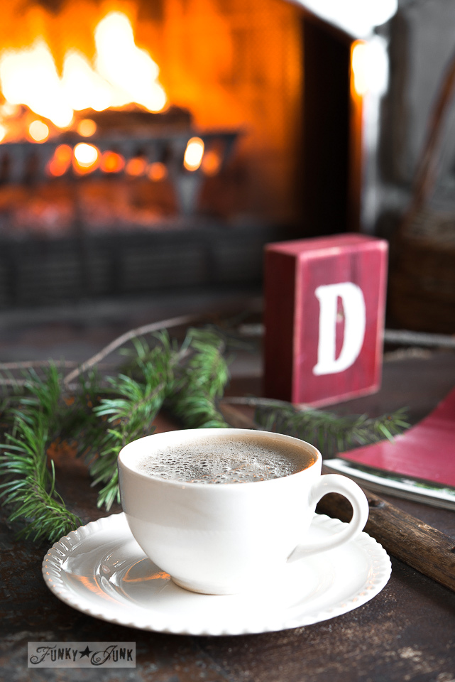 Christmas decorations, sleeping cat and a frothy coffee on an old trunk in front of a lit fireplace / FunkyJunkInteriors.net