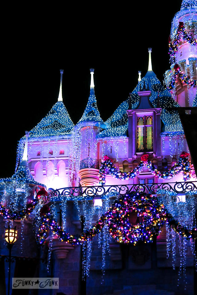 Disneyland castle illuminated at night during Christmas in Disneyland   / FunkyJunkInteriors.net