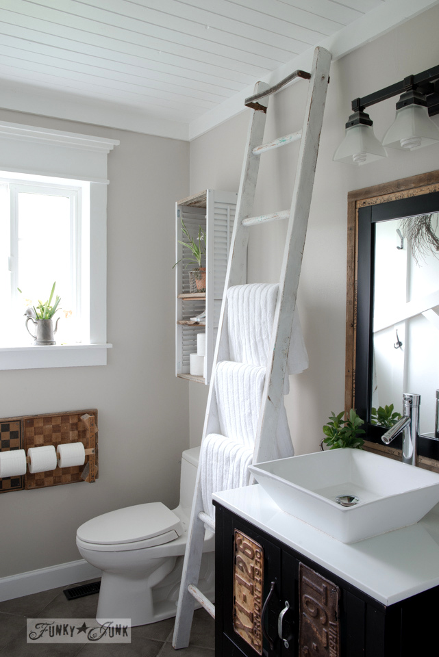 Take the salvaged farmhouse bathroom tour of this pretty master bath with ladder towel hanging, vintage molding and planked ceiling.