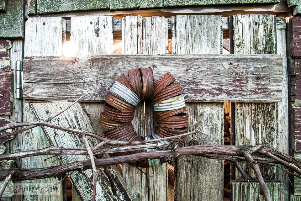 Canning jar lid wreath and rusty lantern on a rustic garden shed / Growing rust in a spring yard / FunkyJunkInteriors.net